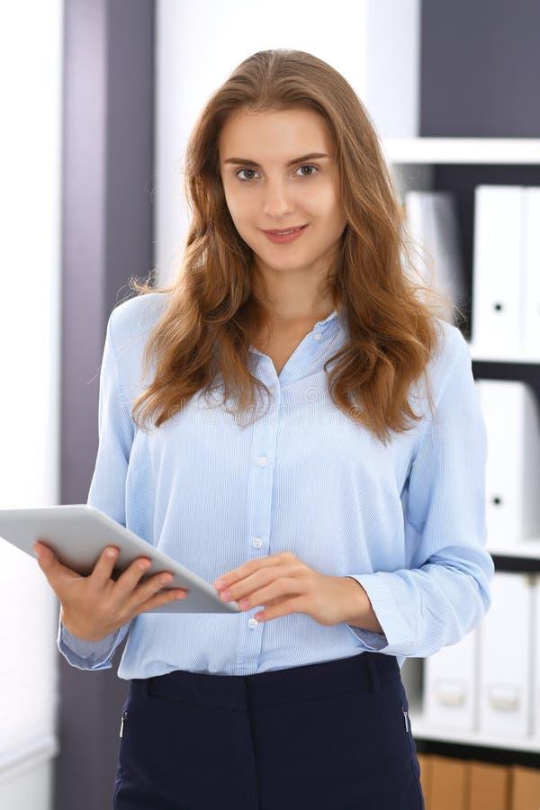 Młodzi brunetki biznesowej kobiety spojrzenia jak studencka dziewczyna przy pracą w biurze Dziewczyna stoi prosto z pastylka komp obraz royalty free