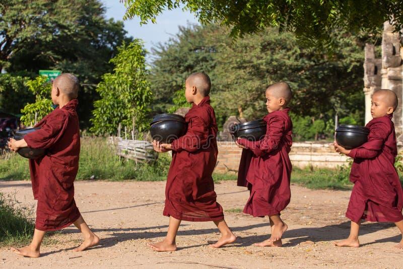 Młodzi buddyjscy nowicjuszi chodzą zbierać datki i ofiary na ulicach Bagan, Myanmar obrazy stock