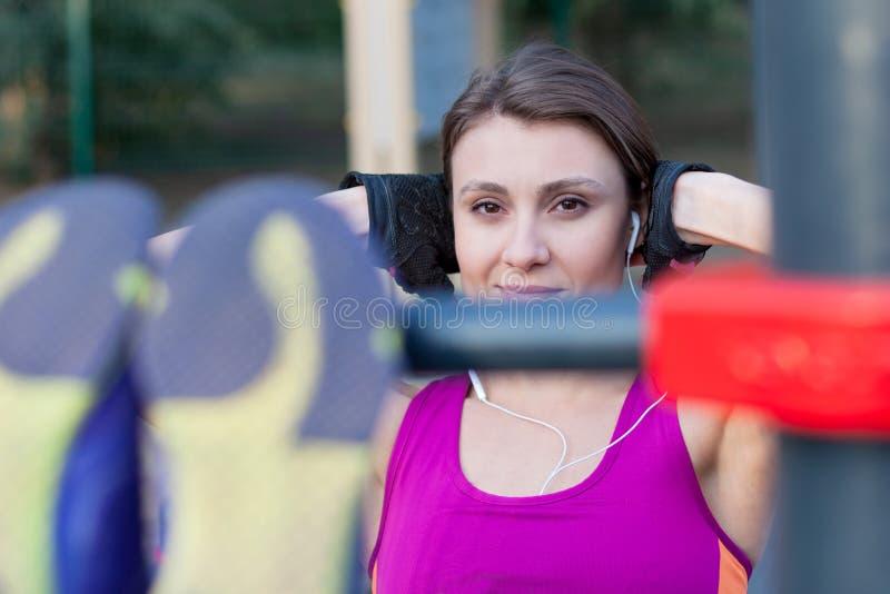 Młodzi caucasian kobieta treningi na parków sportach gruntują, robić brzusznemu szkoleniu Jaskrawy sportswear, ochronne rękawiczk zdjęcia stock