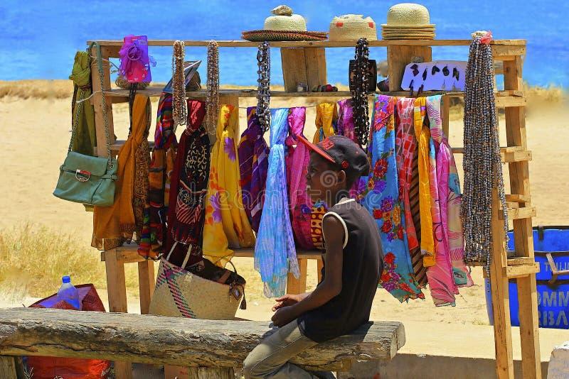 Młodzi chłopiec sprzedawania towary na plaży