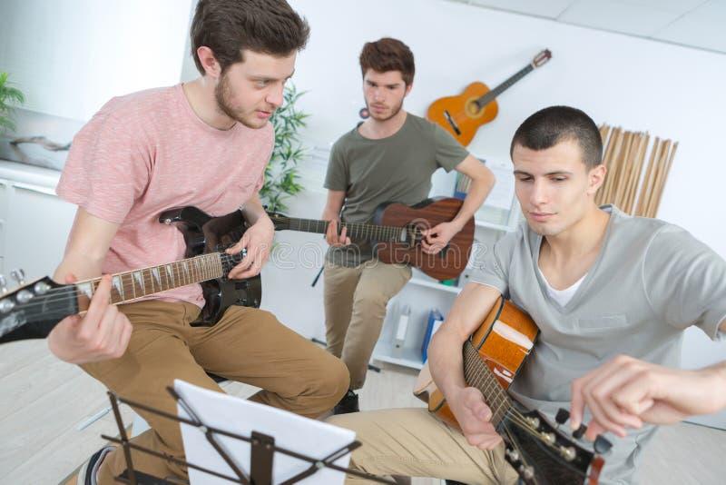 Młodzi człowiecy bawić się gitarę zdjęcia royalty free