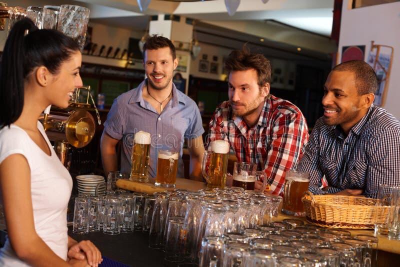 Młodzi człowiecy flirtuje z barmanem w pubie obrazy stock