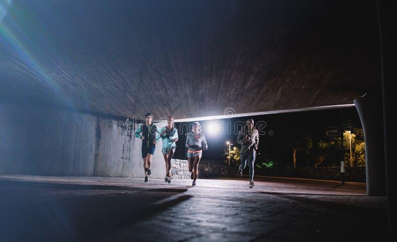 Młodzi człowiecy i kobiety jogging wpólnie przy nocą obrazy royalty free