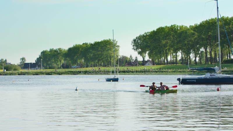 Młodzi człowiecy kajakuje w jeziorze obrazy stock