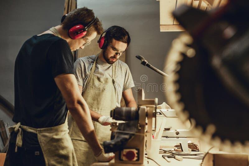 Młodzi człowiecy pracuje na workbench w joinery fotografia royalty free