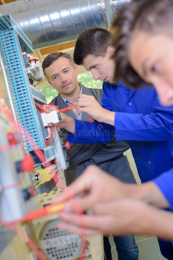 Młodzi człowiecy robi pracie na panel desce zdjęcie stock