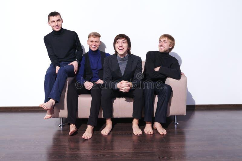 Młodzi człowiecy siedzi na kanapy śmiać się obrazy stock