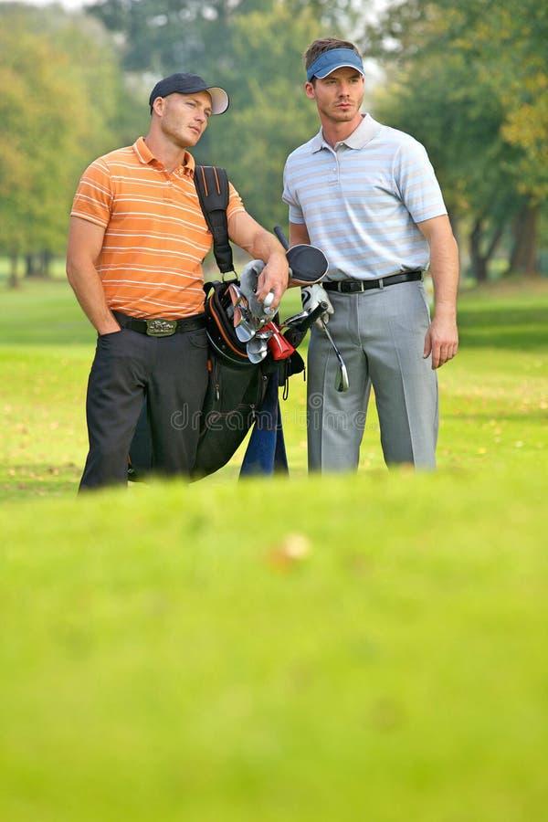 Młodzi człowiecy stoi na pola golfowego przewożenia torbach zdjęcie stock