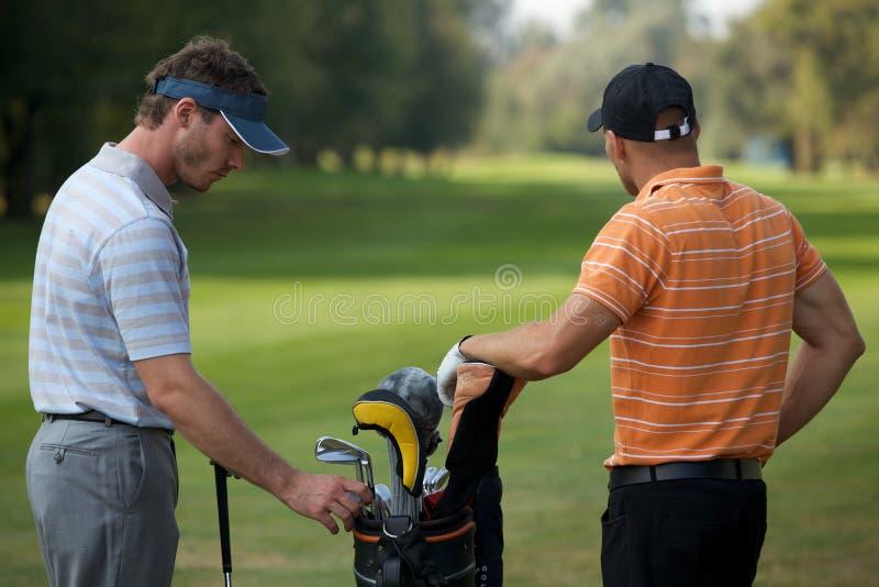 Młodzi człowiecy stoi w polu golfowym golfową torbą kije pełno obrazy royalty free