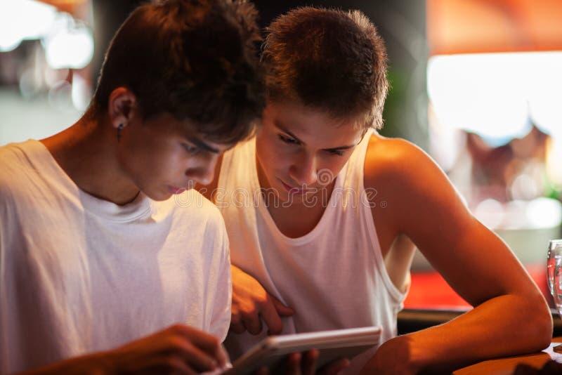 Młodzi człowiecy używa pastylka komputer w kawiarni fotografia royalty free