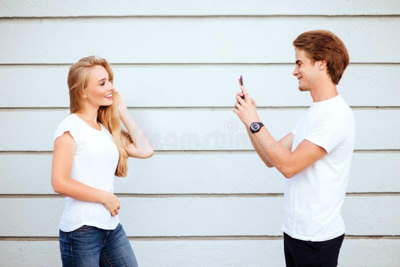 Młodzi dorosli modnisie chłopiec i dziewczyna w białych koszulkach my uśmiechamy się i robić selfie fotografia stock