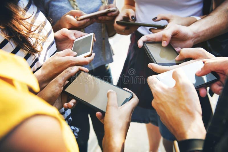 Młodzi dorosli przyjaciele używa smartphones młodości cu wpólnie outdoors zdjęcie stock