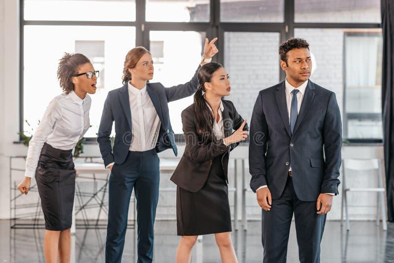 Młodzi emocjonalni biznesmeni kłóci się przy nowożytnym biurem w formalwear obrazy stock