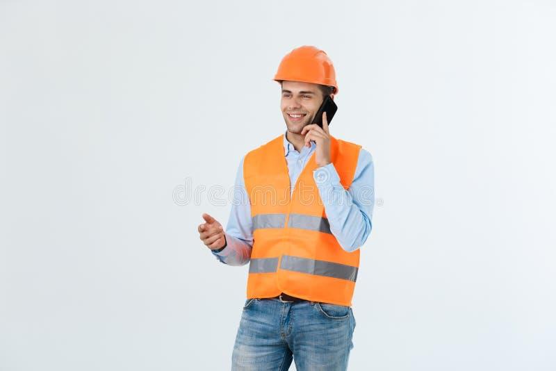 Młodzi inżyniery opowiadają telefonu komórkowego jasnego przodu miejsce robić budynku sukcesowi obrazy stock