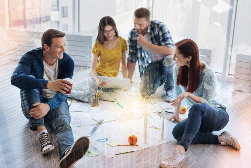 Młodzi koledzy dyskutuje ich projekt zdjęcia stock