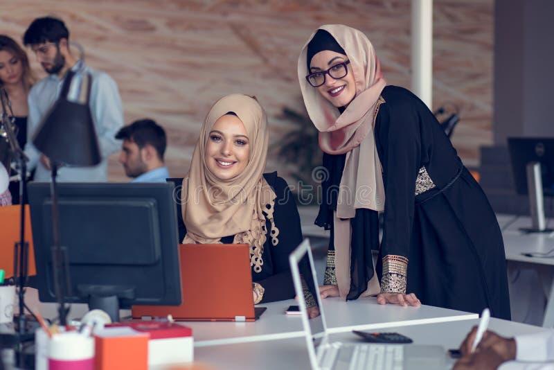 Młodzi kreatywnie początkowi ludzie biznesu na spotkaniu przy nowożytnym biurem robi planom i projektom zdjęcie stock