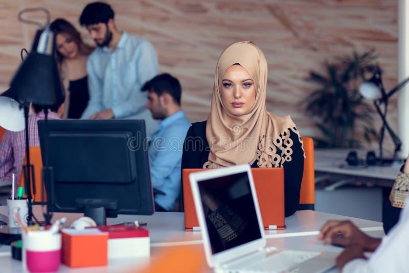Młodzi kreatywnie początkowi ludzie biznesu na spotkaniu przy nowożytnym biurem robi planom i projektom obraz royalty free