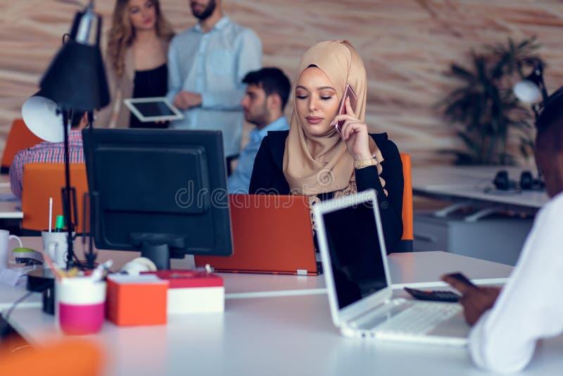 Młodzi kreatywnie początkowi ludzie biznesu na spotkaniu przy nowożytnym biurem robi planom i projektom obraz stock