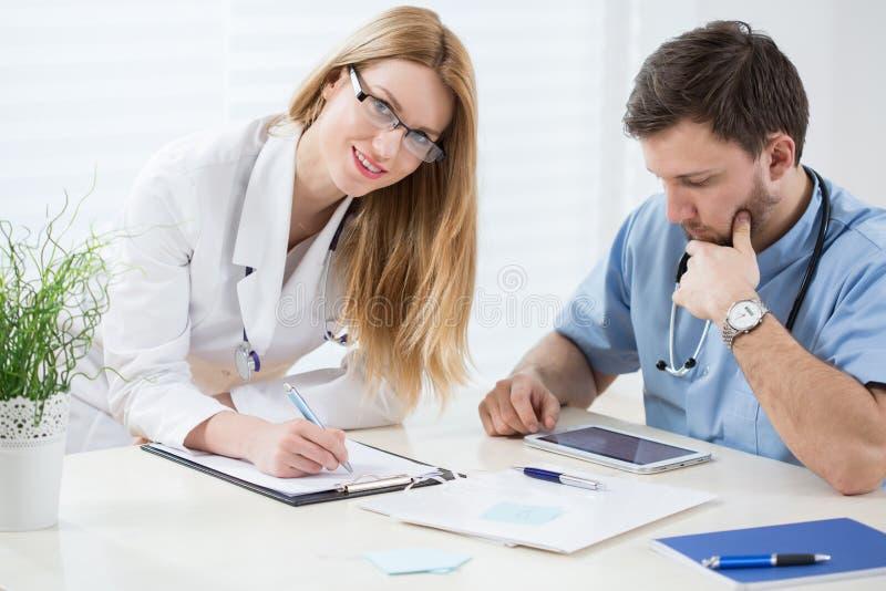 Młodzi lekarzi praktykujący w biurze zdjęcia royalty free