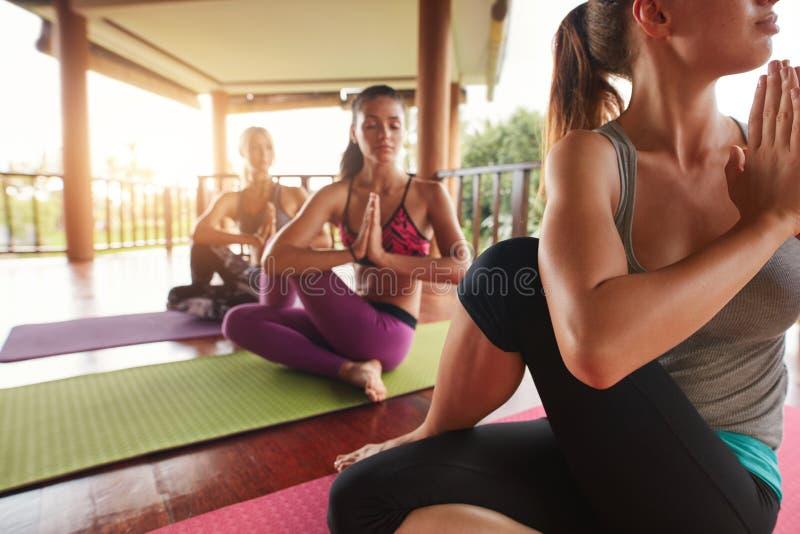 Młodzi ludzie ćwiczy joga w dordzeniowej skręt pozie obraz stock