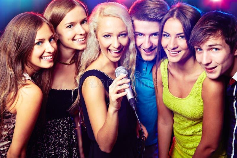 Młodzi ludzie śpiewa przy przyjęciem zdjęcie royalty free