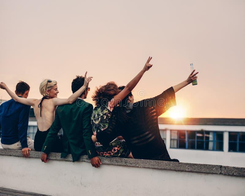 Młodzi ludzie bawi się na tarasie z napojami zdjęcie royalty free