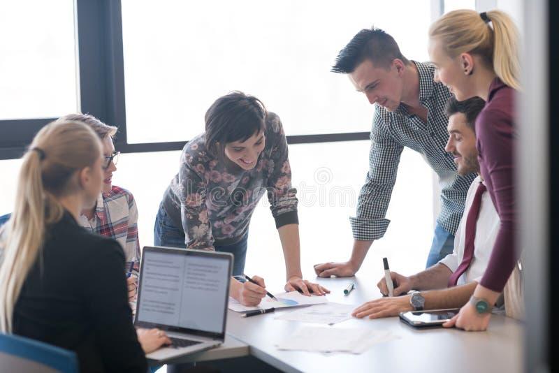 Młodzi ludzie biznesu grupy na spotkaniu przy nowożytnym biurem obraz stock