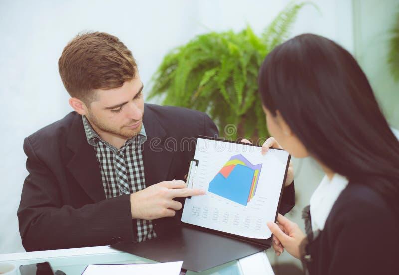 młodzi ludzie biznesu robi spotkania i opowiada dla analizować marketingowego działanie przy biurem na biurku fotografia royalty free