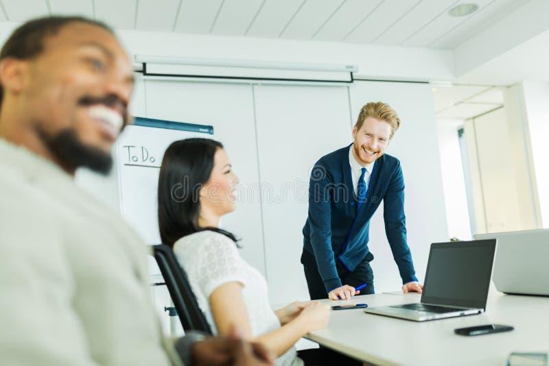 Młodzi ludzie biznesu siedzi przy konferencyjnym stołem uczyć się i obraz stock