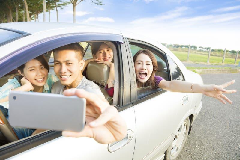 Młodzi ludzie cieszy się wycieczkę samochodową w samochodzie i robi selfie fotografia royalty free