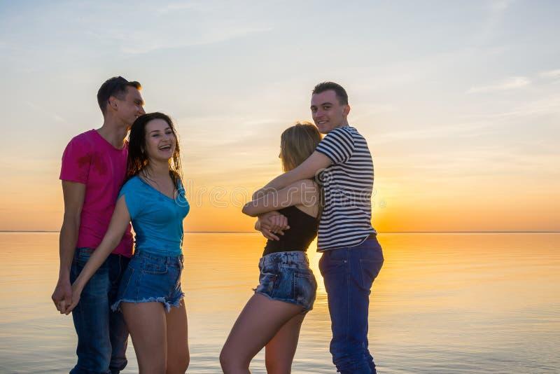 Młodzi ludzie, faceci i dziewczyny, są uściskiem przed morzem przy su obraz royalty free