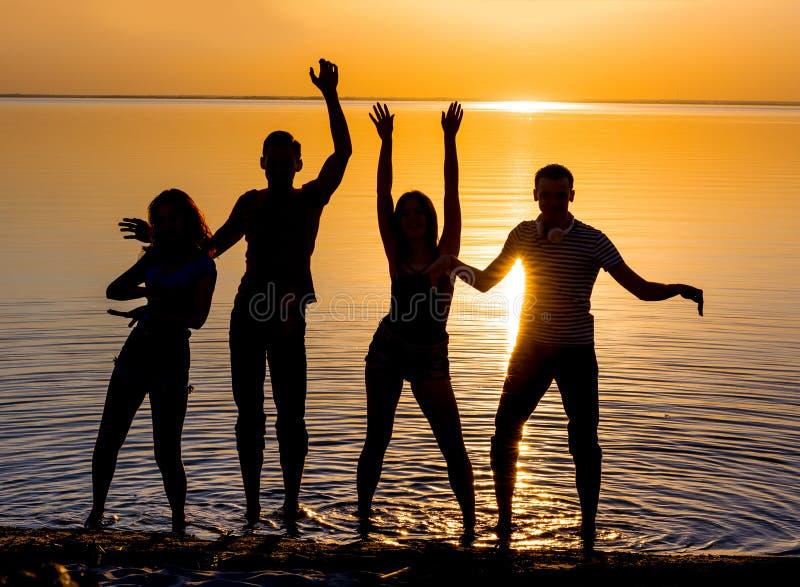 Młodzi ludzie, faceci i dziewczyny, ucznie tanczą na plaży obrazy stock