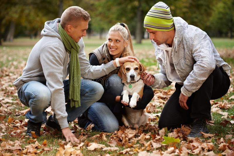Młodzi ludzie i pies w jesień parku obraz stock