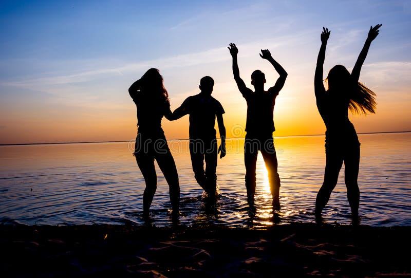 Młodzi ludzie, mężczyzna i kobiety, ucznie tanczą na plaży a fotografia royalty free