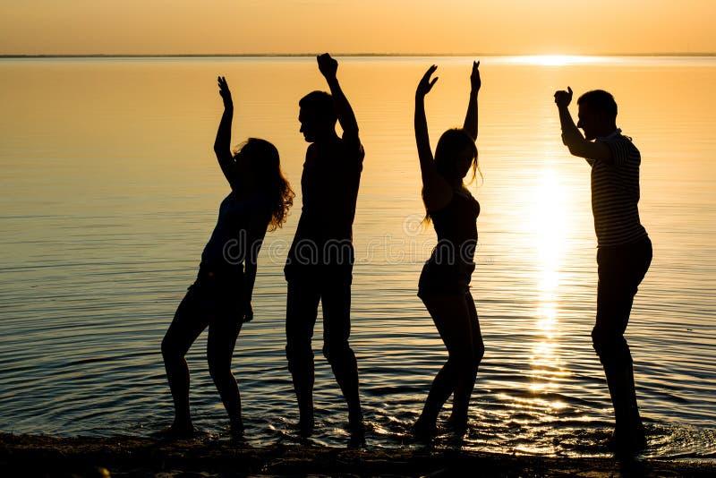 Młodzi ludzie, mężczyzna i kobiety, ucznie tanczą przy zmierzchu plecy obraz royalty free
