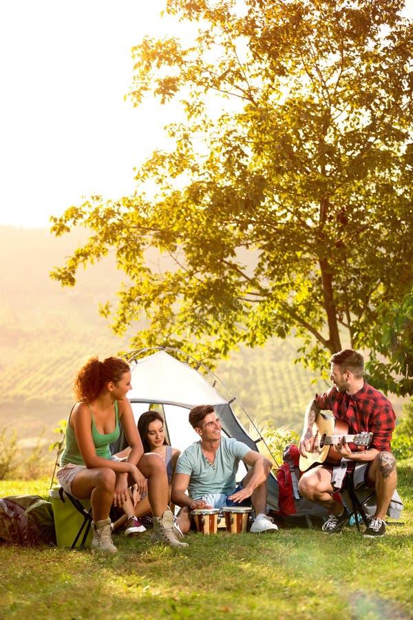 Młodzi ludzie na campingowej wycieczce bawić się i śpiewać fotografia royalty free