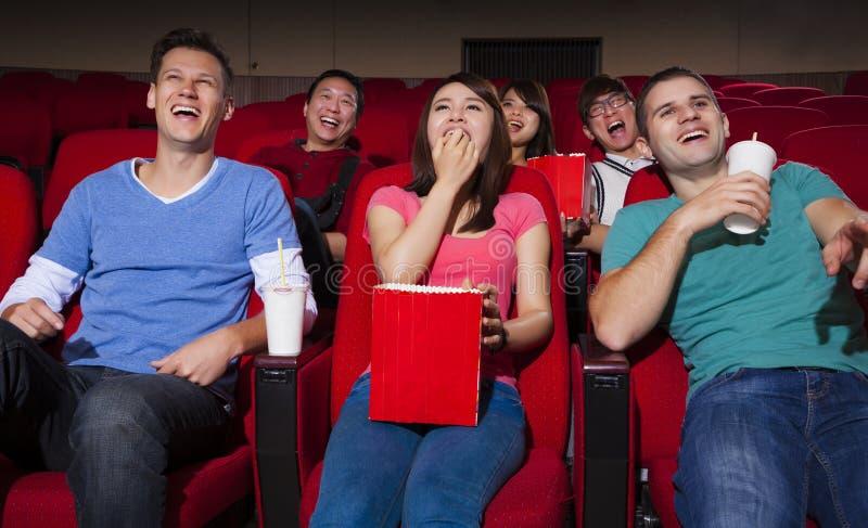 Młodzi ludzie ogląda film przy kinem zdjęcia stock