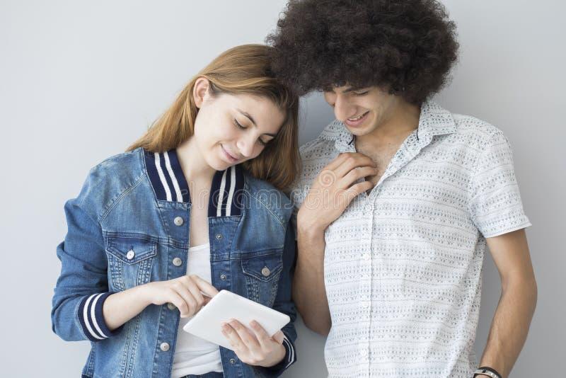 Młodzi ludzie patrzeje pastylkę zdjęcia royalty free