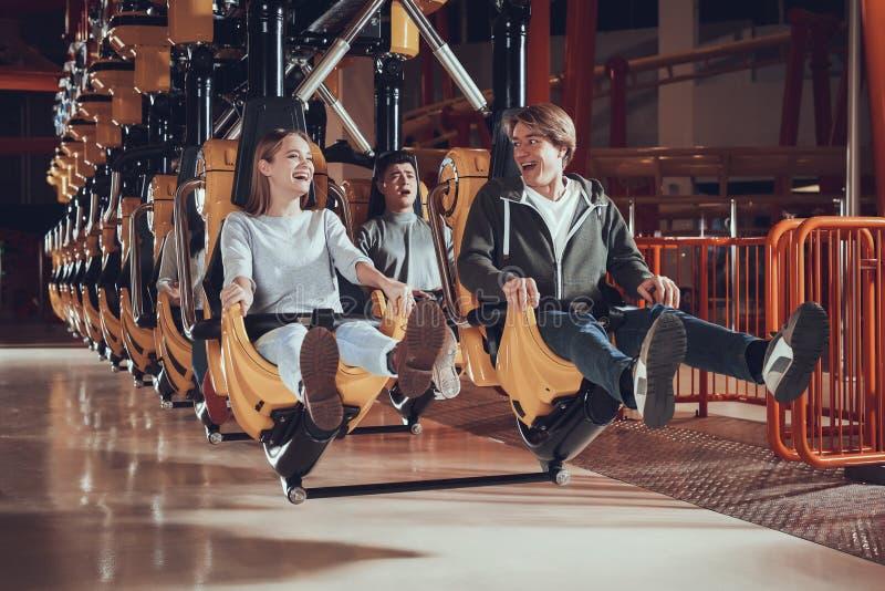 Młodzi ludzie podnoszą ich cieki podczas gdy siedzący na carousel zdjęcie royalty free