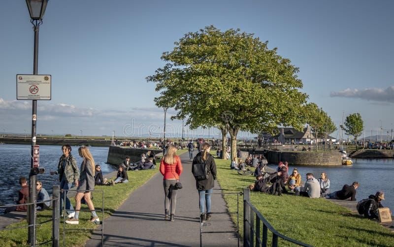 Młodzi ludzie relaksują przy Galway Claddagh na słonecznym dniu 11, 2019 - GALWAY IRLANDIA, MAJ, - fotografia stock
