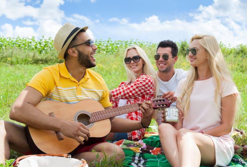 Młodzi ludzie słucha faceta bawić się gitara przyjaciół grupowego letniego dzień zdjęcie stock