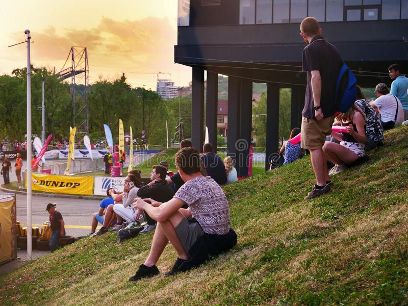Młodzi ludzie siedzą na trawy czekaniu dla samochodów wyścigowych pokazywać up fotografia royalty free