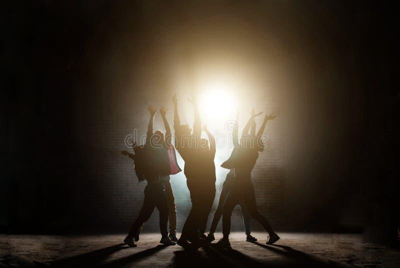 Młodzi ludzie stoi wokoło z nastroszonymi rękami ono modli się wpólnie słońce zdjęcia stock