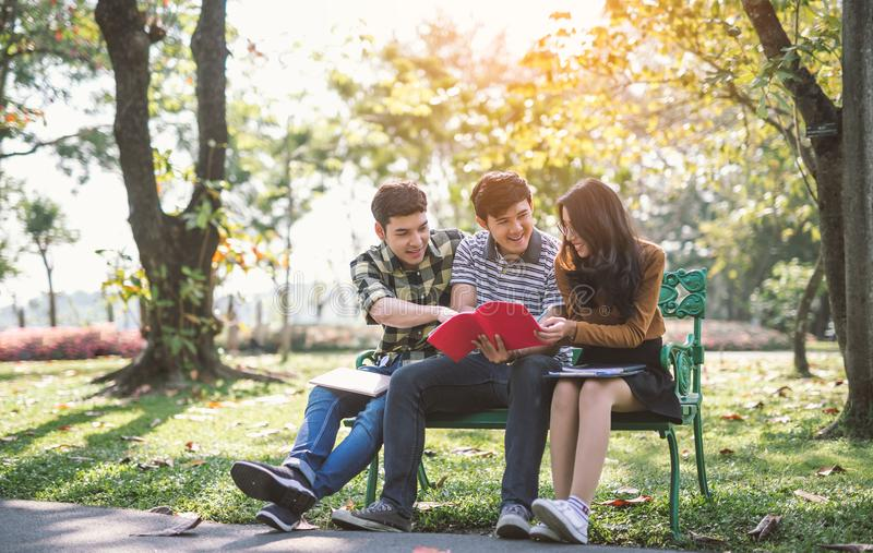 Młodzi ludzie studiuje czytelniczą książkę w parku edukaci nauka czytający obraz royalty free