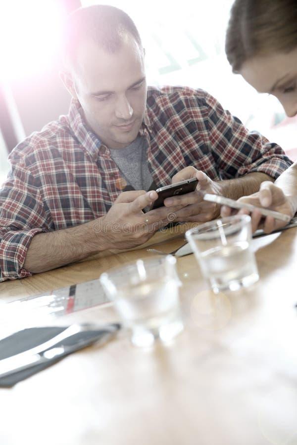 Młodzi ludzie używa ich smartphones zdjęcia stock