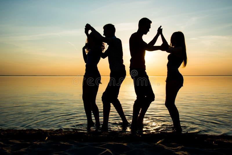 Młodzi ludzie, ucznie tanczą na plaży przy zmierzchu backgr obraz stock