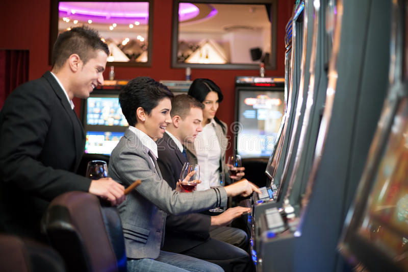 Młodzi ludzie uprawia hazard w kasynie na automat do gier fotografia royalty free