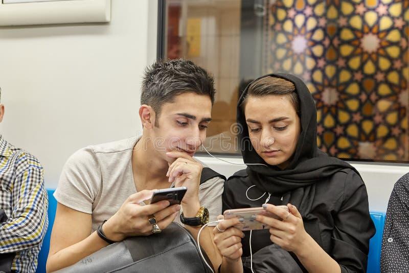 Młodzi ludzie wśrodku pasażerskiego przedziału metro pociąg, Teheran fotografia stock