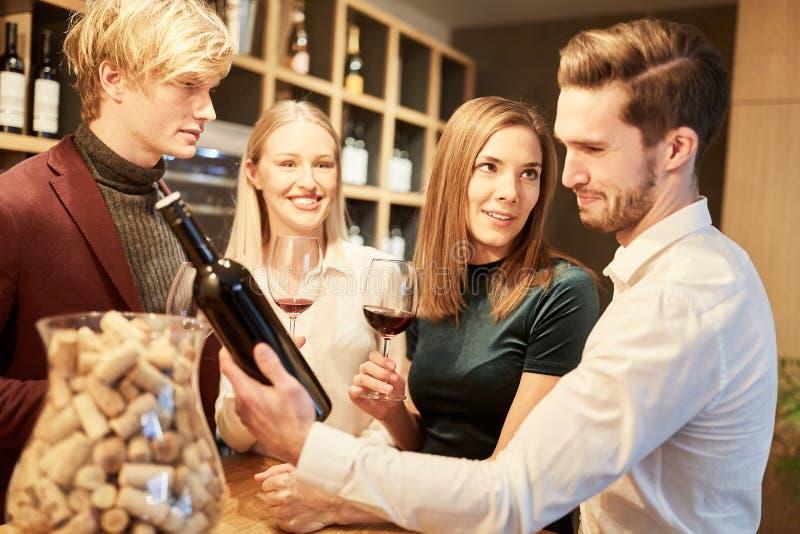 Młodzi ludzie w bistrach przy wino degustacją zdjęcie royalty free