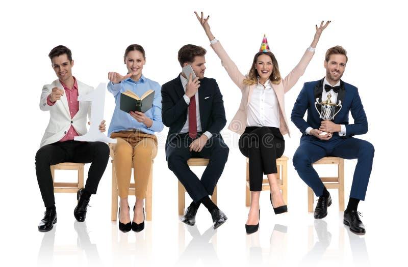 Młodzi ludzie wskazuje, opowiadający na telefonie, odświętności i mieniu tropy, zdjęcie stock